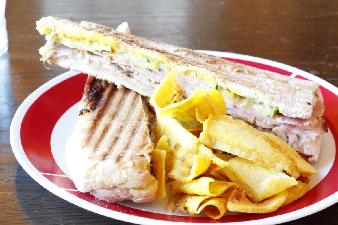 The Cafe Reyes Cuban sandwich, with slow-smoked pork and ham, and a side of sweet plantain chips
