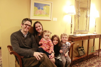 Jackie Penny sits beneath one of her paintings with husband Tony, youngest daughter Lydia and twins Sophia and Henry at the reception for her new Hanover Theatre exhibit.