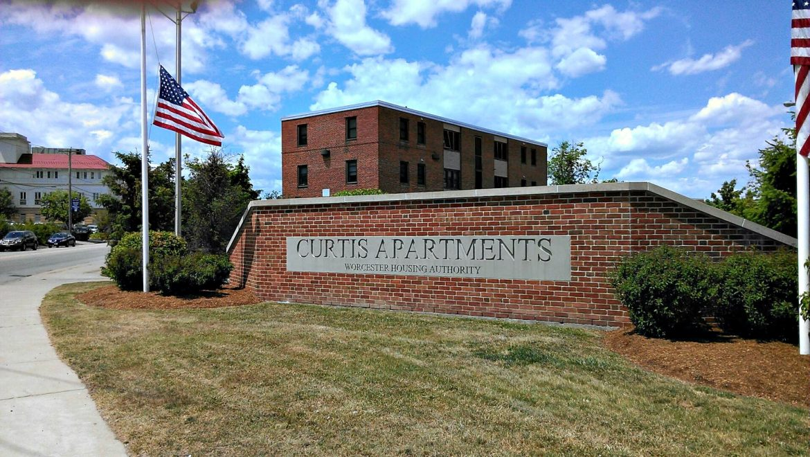 "The words ""Worcester Housing Authority"" are de-emphasized on the sign welcoming visitors to Curtis Apartments in the complex collectively known by most as Great Brook Valley."