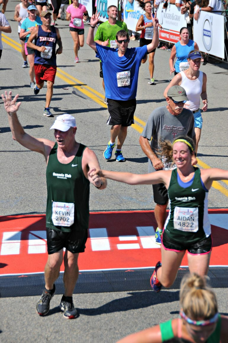 Kevin Bradley, with his daughter Aidan, finishes the Falmouth Road Race last year as part of Team Genesis.