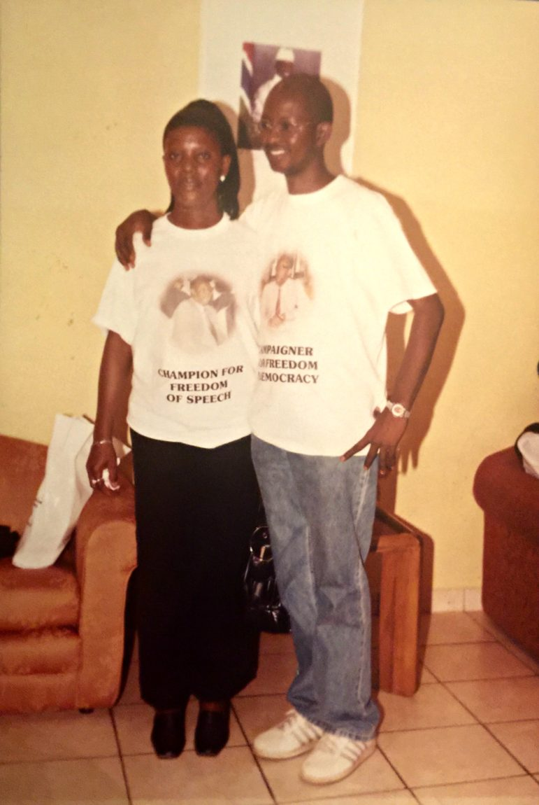 Augustine poses with Theresa, as their secret departure nears, wearing T-shirts at once honoring their former newspaper boss and defying their president (whose photo lurks in the background).