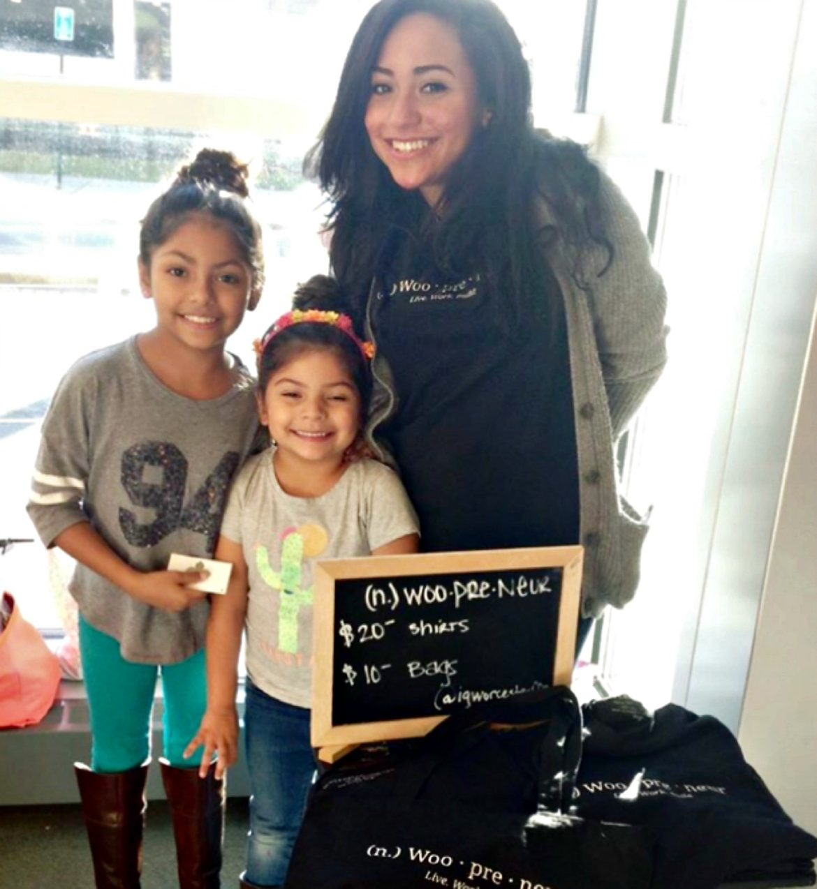 Giselle, with her daughters, Brooklyn, left, and Evian, push their new Woopreneur swag.