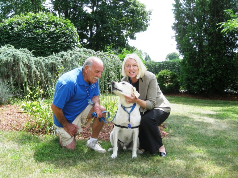 Joe Monfette and Barbara Drapos pose with Cameron the service dog outside the Worcester Senior Center.