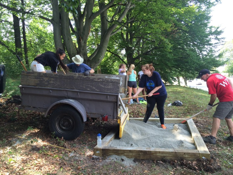 Volunteers pour stone dust in one of the final two platform boxes for the fitness circuit at Newton Hill.
