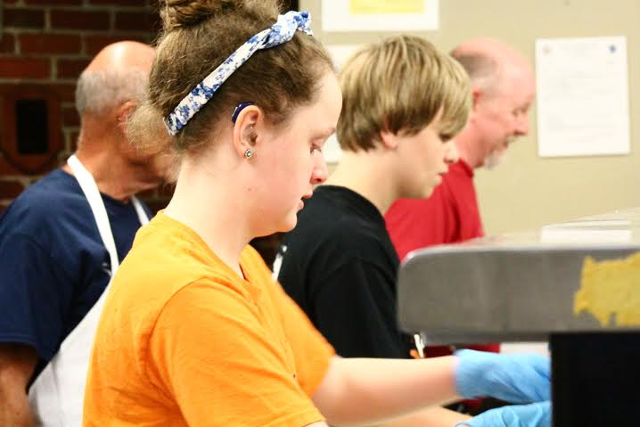 The Davis family, including Kimberly in front, help serve dinner to displaced veterans at Veterans Inc.