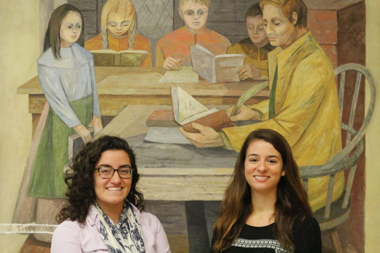 Sarah Valente, left, and Nicole Landry are Holy Cross seniors leading the Magafan Mural Project at Worcester East Middle School.