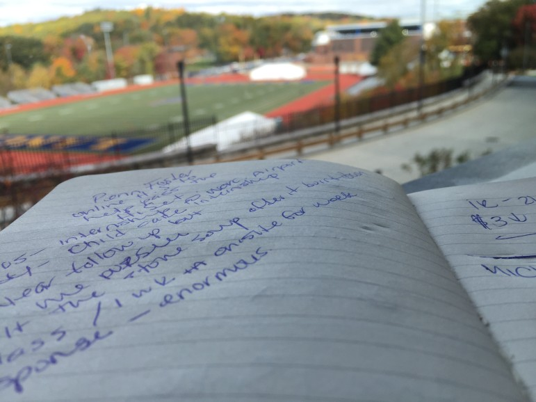With Coughlin Field as a backdrop, Giselle works on homework at Worcester State.