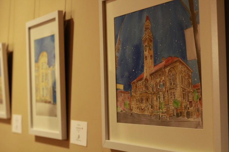A portrait of City Hall hangs next to one of Worcester Public Library in Jackie Penny's Hanover Theatre exhibit.