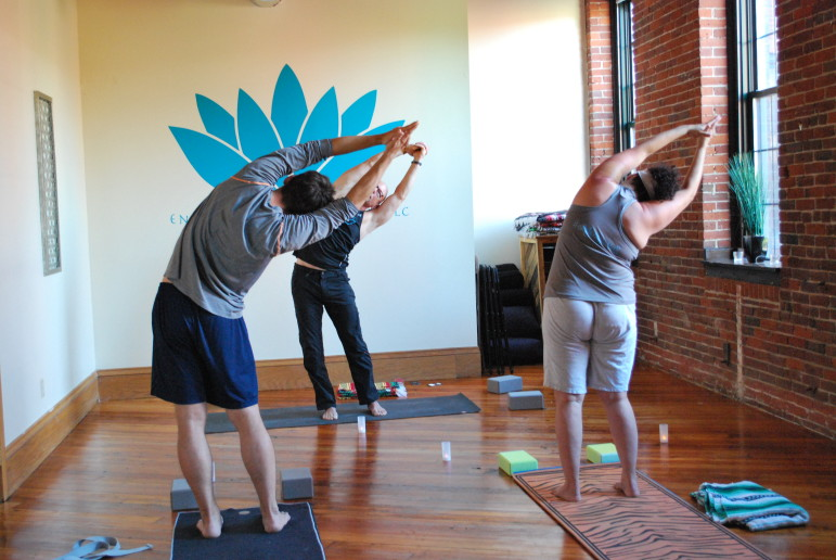 Walter Iwaniki leads a yoga class at Enlightened Interventions, a new type of wellness center, on Union Street.
