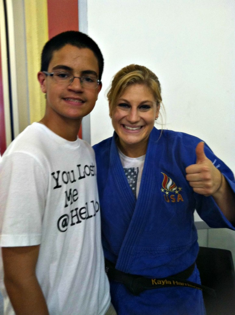 Kayla Harrison, posing with a fan, will speak at Assumption College this week.