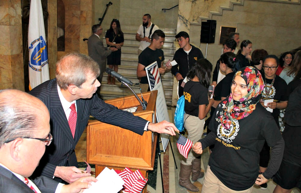 Secretary of State William F. Galvin hands out American flags to students at the State House on Flag Day, June 14.