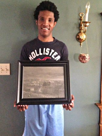 Asylum seeker Jeffry poses with a picture of the place that he now calls home.
