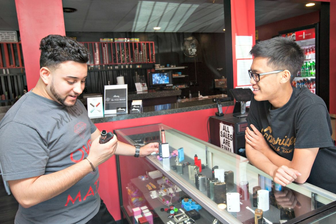 Vaporize owner Adrian Pelka, right, talks with a customer Friday, June 24.