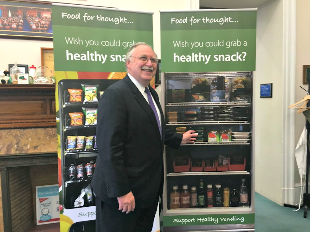 <cutline: Rep. Stephen Kulik poses in his office with banners designed to raise awareness of legislation promoting healthier vending machine options.