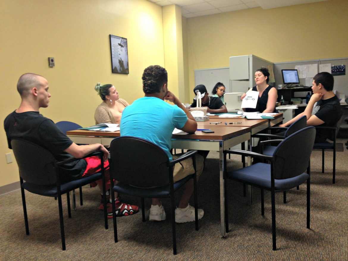 Case manager Lila Milukas, center, during a weekly YouthWorks education/training session, with participants, clockwise from far right, Jonathan Valladares, Bobby Harris, James Fenner, Shelby Onstott and Jean-Carlos Gomez.
