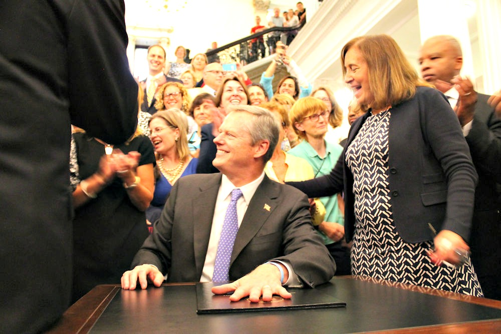 "Treasurer Deb Goldberg gives Gov. Charlie Baker a slap on the back after he signed the pay equity act Aug. 1. ""It is the law!"" Baker said as he closed the act's folder."