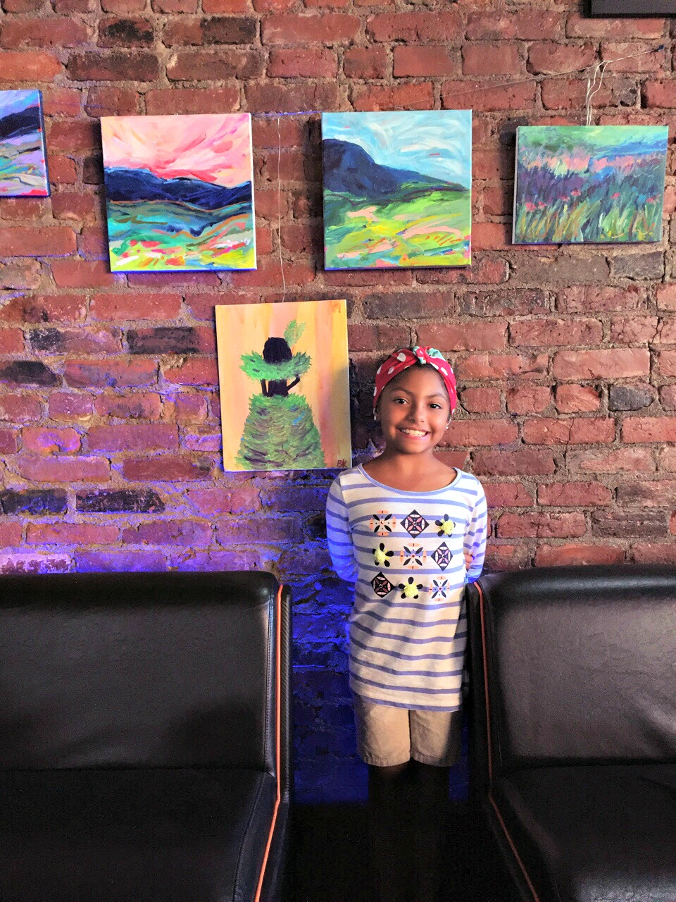Brooklyn stands in front of the art she exhibited during the Worcester Pride art show.