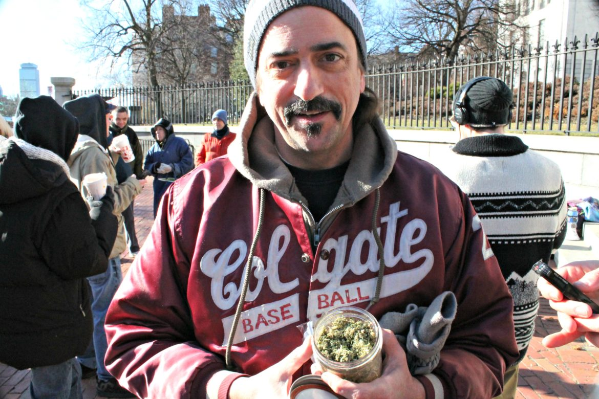 Keith Saunders holds a jar of what he said was nearly an ounce of newly legalized marijuana outside the State House Dec. 15.